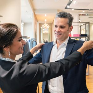 Elegant man buying a suit and having it tailored at the clothing store – shopping concepts