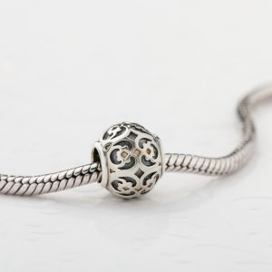 Silver charm bead with ornament for chain bracelet. Product concept for jeweler