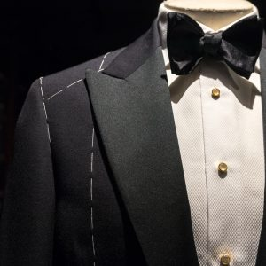 Close up on top part of tailored jacket on mannikin with black bow tie and sequined buttons on shirt