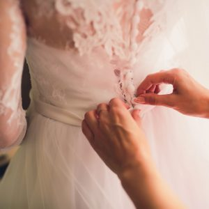 Gorgeous, blonde bride in white luxury dress is getting ready for wedding. Morning preparations. Woman putting on dress