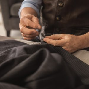 Mature tailor sewing at table in atelier