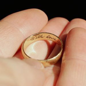 "A man holds a wedding ring engraved ""with love"""