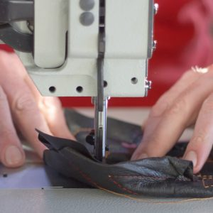 Sewing machine in a leather workshop in action with hands working with a leather details. Leather craft.
