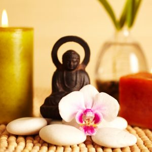 Spa still life buddha statue and river rock, bamboo in vase, and candles, and orchid flower