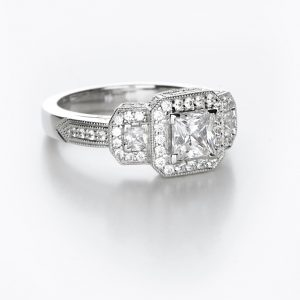 A contemporary diamond ring with a princess cut center stone and pave accents.