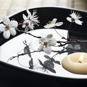 SEVERAL MORE IN THIS SERIES. Cherry blossom flower arrangement with floating aromatherapy candle in a serene asian-style zen spa.  Shallow DOF.