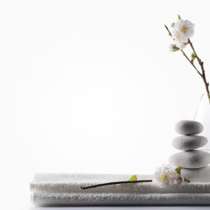 """SEVERAL MORE IN THIS SERIES. Clean zen spa background concept, with white massage stones, cherry blossoms and towel.  Copy space."""
