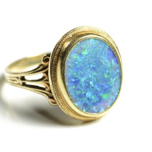Opal and yellow gold ring.  On a white background.