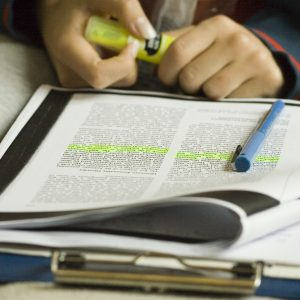 Shot of a student highlighting text while studying