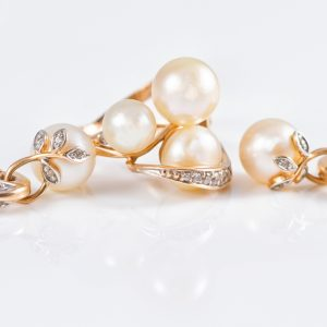 Elegant gold rings and gold earrings with pearls reflected in a white surface