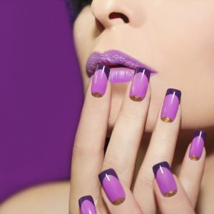 Mauve lip and French manicure with gold glitter on a purple background.