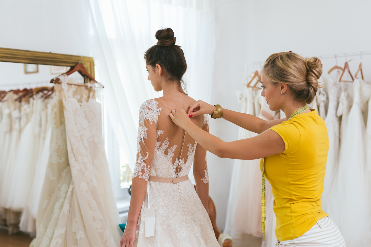 A young bride being helped into her wedding dress in clothes shop