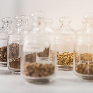 Glass close jars with coffee-seeds on white table