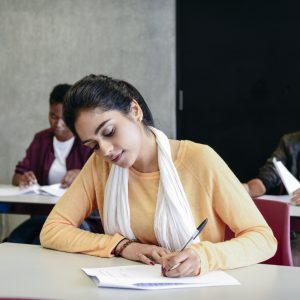 Young Indian woman writing on paper, concentrating, with two students in background
