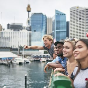 Excited multi-ethnic friends looking away against buildings. Happy males and females are standing on bridge over river. They are traveling together in city.
