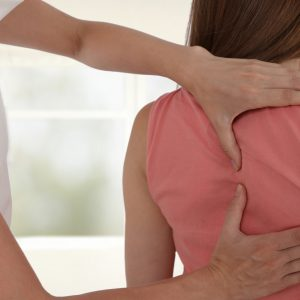 Woman having chiropractic back adjustment. Osteopathy, Physiotherapy, sport injury rehabilitation concept