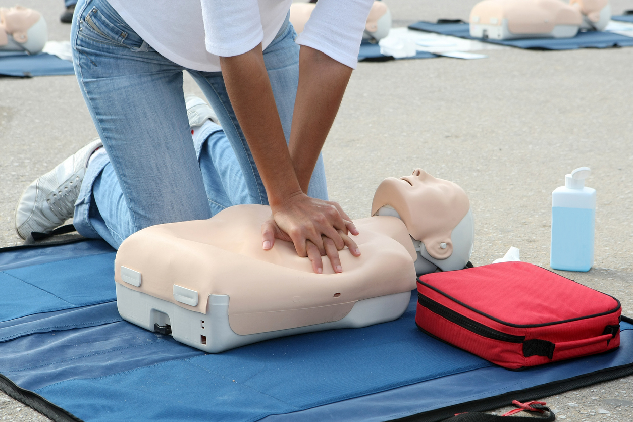 Female instructor showing CPR on training doll